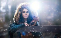 Belle jeune fille avec le cap brun de fourrure appréciant le paysage d'hiver se reposant sur le banc en parc Adolescente posant,  photo stock