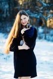 Belle jeune fille avec le sphinx de Don de race de chat sur ses mains en hiver en parc Photographie stock libre de droits
