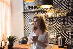Belle jeune fille avec les cheveux bouclés se tenant dans la cuisine au fourneau Photos stock