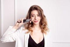 Belle jeune fille avec les cheveux bruns dans des ses mains tenant une brosse professionnelle de maquillage image stock