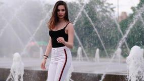Belle jeune fille avec les cheveux foncés à la fontaine Mouvement lent clips vidéos