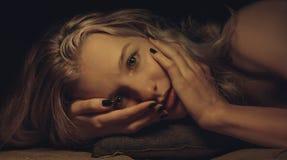 Belle jeune fille avec les configurations sensibles et longs les cheveux onduleux, d'intérieur, studio photographie stock