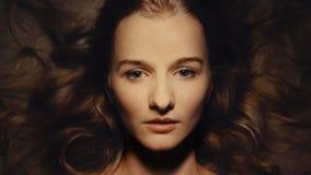 Belle jeune fille avec les configurations sensibles et longs les cheveux onduleux, d'intérieur, studio photo stock