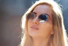 Belle jeune fille avec les verres de port de longs cheveux, posant à la rue dans le jour ensoleillé Copiez l'espace images libres de droits