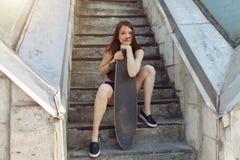 Belle jeune fille avec un long conseil dans la ville Le concept de la jeunesse moderne Vacances actives d'amusement photographie stock