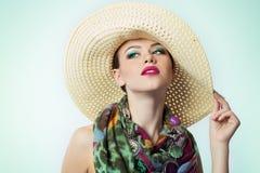 Belle jeune fille avec un maquillage lumineux de chapeau avec la belle écharpe chère de couleur au cou sur le fond blanc dans le  Photographie stock libre de droits