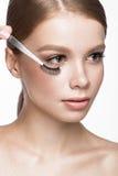 Belle jeune fille avec un maquillage naturel léger, des brucelles de sourcil et des cils faux Visage de beauté Photo stock