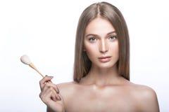 Belle jeune fille avec un maquillage naturel léger et des outils de beauté à disposition Photo libre de droits