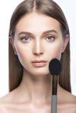 Belle jeune fille avec un maquillage naturel léger et des outils de beauté à disposition Photographie stock