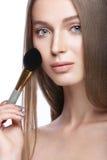 Belle jeune fille avec un maquillage naturel léger et des outils de beauté à disposition Photo stock
