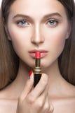 Belle jeune fille avec un maquillage naturel léger et des outils de beauté à disposition Images stock