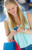 Belle jeune fille ayant l'amusement avec le smartphone Photo stock