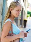 Belle jeune fille ayant l'amusement avec le smartphone Images libres de droits