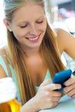 Belle jeune fille ayant l'amusement avec le smartphone Photographie stock
