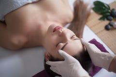 Belle jeune fille ayant le massage de visage dans le salon de station thermale Photographie stock libre de droits