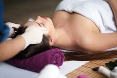 Belle jeune fille ayant le massage de visage dans le salon de station thermale Photos stock
