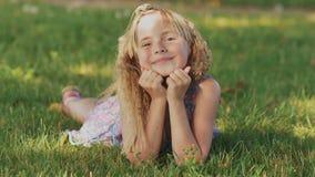 Belle jeune fille blonde se trouvant sur un champ, herbe verte Appréciez dehors la nature Fille de sourire en bonne santé se situ banque de vidéos