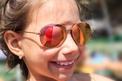 Belle jeune fille dans des lunettes de soleil avec le rerlection de ballon de plage images stock