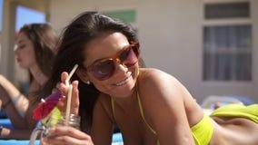 Belle jeune fille dans des lunettes de soleil buvant des cocktails avec ses amis féminins détendant par la piscine Piscine d'été banque de vidéos
