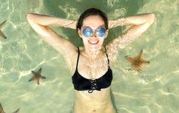 Belle jeune fille dans des lunettes de soleil se situant dans l'eau sur le dos et le sourire Les étoiles de mer sont autour Photos libres de droits