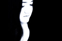 Belle jeune fille dans des sons bleus contre le noir Photographie stock libre de droits