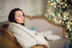 Belle jeune fille dans des vacances de attente de Noël de plaid mou Arbre de Noël sur le fond Image libre de droits
