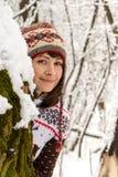 Belle jeune fille dans l'usage confortable tricoté regardant par derrière l'arbre en portrait neigeux de forêt de fille de sourir photos libres de droits