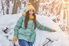 Belle jeune fille dans le chapeau tricoté sur le fond de forêt d'hiver photo stock