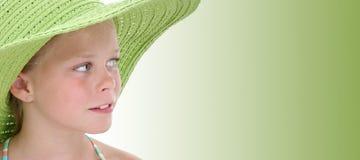 Belle jeune fille dans le grand chapeau vert de plage au-dessus du vert Image libre de droits
