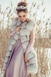 Belle jeune fille dans le manteau d'hiver avec la couronne et le bouquet Photographie stock libre de droits