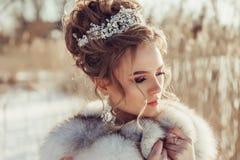 Belle jeune fille dans le manteau d'hiver avec la couronne et le bouquet Image stock