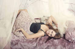 Belle jeune fille dans les rideaux Photographie stock