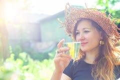 Belle jeune fille dans un chapeau de paille avec un verre de boisson dans un jardin d'été Images stock
