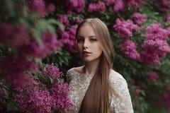 Belle jeune fille dans un lilas fleurissant Photos libres de droits