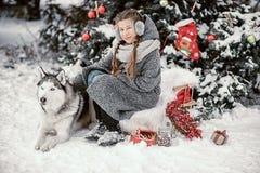 Belle jeune fille dans un manteau gris dans la forêt d'hiver avec le chien de traîneau sibérien Symbole de la nouvelle année 2018 Photographie stock