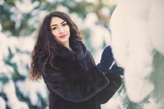 Belle jeune fille dans une forêt neigeuse Image libre de droits