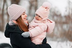 Belle jeune fille dans une salopette rose jouant avec sa mère en parc neigeux d'hiver image stock