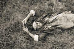 Belle jeune fille de boho dans la veste se couchant sur l'herbe photos libres de droits