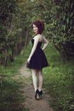 Belle jeune fille de brune dans la robe noire courte marchant par les bois Photographie stock libre de droits