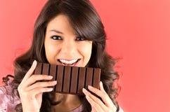 Belle jeune fille de brune mangeant du chocolat Photo stock