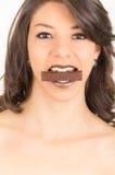 Belle jeune fille de brune mangeant du chocolat Photographie stock