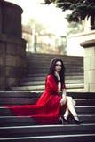 Belle jeune fille de brune s'asseyant sur les escaliers Photos stock