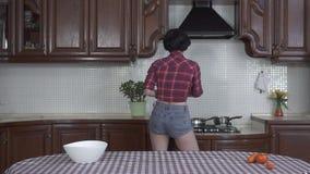 Belle jeune fille de danse dans des écouteurs portant une chemise de plaid et un découpage en tranches de shorts légumes sur un c banque de vidéos