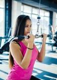 Belle jeune fille de forme physique dans le gymnase faire des exercices de machine de lat Images libres de droits