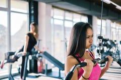 Belle jeune fille de forme physique dans le gymnase faire des exercices de machine de lat images stock