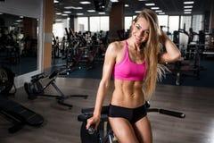 Belle jeune fille de forme physique souriant et se reposant après des exercices accroupis Images stock