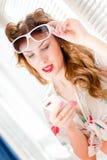 Belle jeune fille de pin-up ayant le message de lecture d'amusement au téléphone portable mobile et portant la photo de portrait  Photographie stock libre de droits
