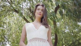 Belle jeune fille de portrait avec de longs cheveux de brune portant une longue position blanche de robe de mode d'été sous banque de vidéos