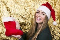 Belle jeune fille de sourire avec de longs cheveux dans un chapeau de Santa Claus Image libre de droits