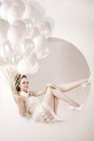 Belle jeune fille de sourire moderne à la mode avec des ballons dans le saut Image stock